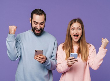 man and woman each winning a Grande Vegas game on their phone